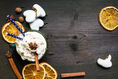 Bożenarodzeniowa filiżanka z batożącą śmietanką, cynamon, kakaowy proszek, anyż, wysuszonej pomarańcze ang piernikowi ciastka na  obraz stock