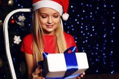 Bożenarodzeniowa fotografia śliczna mała blond dziewczyna w Santa kapeluszu i czerwieni smokingowy mienie prezent - boksuje na ba Fotografia Stock
