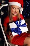 Bożenarodzeniowa fotografia śliczna mała blond dziewczyna w Santa kapeluszu i czerwieni smokingowy mienie prezent - boksuje na ba Zdjęcie Royalty Free