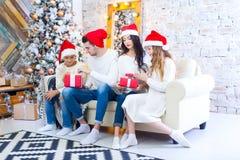 Bożenarodzeniowa fotografia piękna rodzina z dwa dziećmi w Święty Mikołaj czerwieni nakrętkach i czerwieni teraźniejszość Siedzi  Obraz Royalty Free