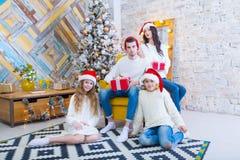 Bożenarodzeniowa fotografia piękna rodzina z dwa dziećmi w Święty Mikołaj czerwieni nakrętkach i czerwieni teraźniejszość Siedzi  Zdjęcie Stock