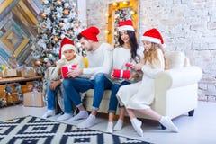 Bożenarodzeniowa fotografia piękna rodzina z dwa dziećmi w Święty Mikołaj czerwieni nakrętkach i czerwieni teraźniejszość Siedzi  Obrazy Royalty Free