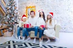 Bożenarodzeniowa fotografia piękna rodzina z dwa dziećmi w Święty Mikołaj czerwieni nakrętkach i czerwieni teraźniejszość Siedzi  obraz stock