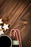 Bożenarodzeniowa gorąca parująca filiżanka glint wino z pikantność, anyż, ciastka w kształcie gwiazda, czerwoni cukierki, pieprz  zdjęcie royalty free
