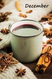 Bożenarodzeniowa gorąca parująca filiżanka glint wino z pikantność, cynamon, anyż, ciastka w kształcie gwiazda, czerwoni cukierki zdjęcie stock
