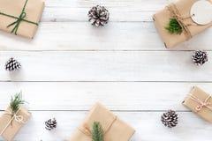 Bożenarodzeniowa jodła opuszcza na białym nieociosanym drewnianym tle, sosna rożki i prezent Fotografia Stock