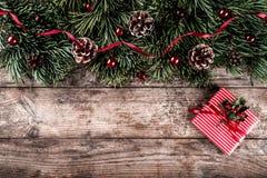 Bożenarodzeniowa jodła rozgałęzia się na wakacyjnym drewnianym tle z prezentów pudełkami, sosnowi rożki, czerwona dekoracja obrazy royalty free