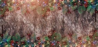 Bożenarodzeniowa jodła rozgałęzia się z światłami i czerwieni dekoracjami na drewnianym tle Xmas i Szczęśliwa nowy rok rama zdjęcie royalty free
