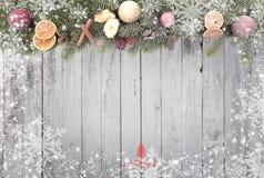 Bożenarodzeniowa jodła rozgałęzia się z białymi płatkami śniegu jako granica przeciw drewnianemu tłu z czerwoną choinką troszkę fotografia stock