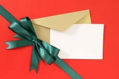 Bożenarodzeniowa lub urodzinowa karta na czerwonym prezenta opakunku papieru tle, zielonego prezenta tasiemkowy łęk, biel kopii p Zdjęcie Royalty Free