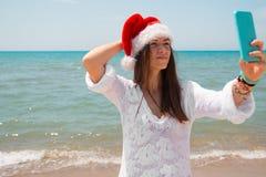 Bożenarodzeniowa młoda uśmiechnięta kobieta w czerwonym Santa obrazka jaźni kapeluszowym bierze portrecie na smartphone przy plaż obraz royalty free