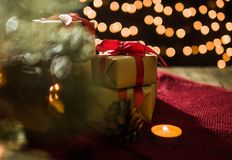 Bożenarodzeniowa prezenta pudełka dekoracja i świeczka na czerwonym szaliku z bokeh zaświecamy tło Zdjęcie Royalty Free