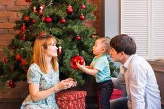 Bożenarodzeniowa rodzina z dzieckiem Szczęśliwi ono Uśmiecha się rodzice i dzieci Świętuje nowego roku w domu Święta moje portfol Zdjęcie Royalty Free