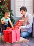 Bożenarodzeniowa rodzina z dzieckiem Szczęśliwy dziecka otwarcia prezent Święta moje portfolio drzewna wersja nosicieli Obraz Royalty Free