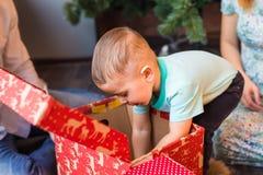 Bożenarodzeniowa rodzina z dzieckiem Szczęśliwy dziecka otwarcia prezent Święta moje portfolio drzewna wersja nosicieli Obrazy Royalty Free