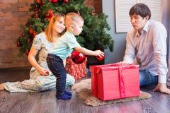 Bożenarodzeniowa rodzina z dzieckiem Z prezentem szczęśliwy dziecko Święta moje portfolio drzewna wersja nosicieli Obraz Stock