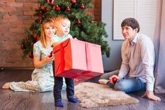 Bożenarodzeniowa rodzina z dzieckiem Z prezentem szczęśliwy dziecko Święta moje portfolio drzewna wersja nosicieli Obrazy Stock
