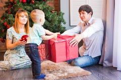 Bożenarodzeniowa rodzina z dzieckiem Z prezentem szczęśliwy dziecko Święta moje portfolio drzewna wersja nosicieli Fotografia Stock