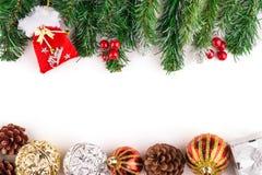 Bożenarodzeniowa sezonowa granica holly, bluszcz, jemioła, cedrowi liści sprigs z sosna rożkami i złociści baubles, Zdjęcie Stock