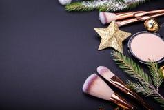 Bożenarodzeniowa sprzedaż kosmetyki i muśnięcia Set kosmetyki z Bożenarodzeniową dekoracją na czarnym tle obrazy royalty free
