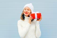 Bożenarodzeniowa szczęśliwa uśmiechnięta młoda kobieta jest ubranym trykotowego kapeluszowego pulower nad błękitem z prezenta pud Zdjęcia Stock
