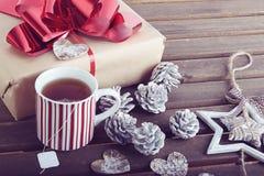 Bożenarodzeniowa teraźniejszość, dekoracja i ciepła herbata na drewnianym tle, Zdjęcia Stock