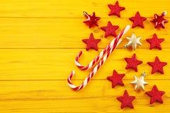 Bożenarodzeniowe cukierek trzciny, gwiazdy na żółtym tle i fotografia royalty free