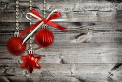 Bożenarodzeniowe dekoracje i czerwony tasiemkowy łęk na drewnie Zdjęcia Royalty Free