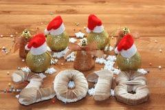 Bożenarodzeniowe dekoracje, Santa ` s kapelusze na piłkach nowy rok 2018, drewniany tło zdjęcia royalty free