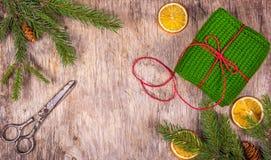Bożenarodzeniowe dekoracje z jedlinowym drzewem i prezentem na drewnianej desce Prezenta pakunek i starzy nożyce zdjęcie royalty free