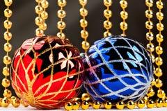 Bożenarodzeniowe piłki i złota girlanda z lekkimi promieniami na ciemnym tle Obrazy Stock