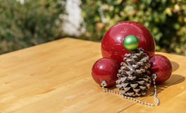 Bożenarodzeniowe piłki obok pinecone na drewnianym stole Zdjęcie Royalty Free