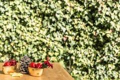 Bożenarodzeniowe piłki, pinecone, puchary i gwiazda na stole w przodzie, Zdjęcia Stock