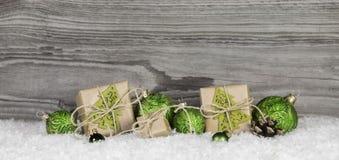 Bożenarodzeniowe teraźniejszość i zielone piłki na drewnianym starym popielatym tle zdjęcie stock