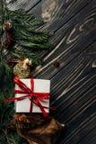 Bożenarodzeniowe teraźniejszość z czerwonym faborkiem i złoci ornamenty na styli Zdjęcie Stock