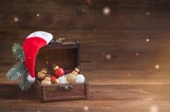 Bożenarodzeniowe wakacyjne piłki w starej drewnianej klatce piersiowej z Święty Mikołaj kapeluszem na nieociosanym tle, pocztówko zdjęcie royalty free
