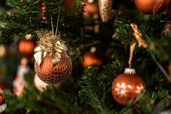 Bożenarodzeniowego brązu balowy obwieszenie na sośnie rozgałęzia się z świątecznym tłem zdjęcia stock