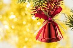 Bożenarodzeniowego dzwonu ornamentu zrozumienie na gałąź z żółtymi bokeh półdupkami Zdjęcie Royalty Free