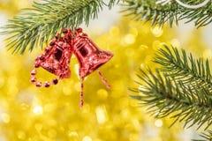 Bożenarodzeniowego dzwonu ornamentu zrozumienie na gałąź z żółtymi bokeh półdupkami Zdjęcie Stock