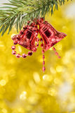 Bożenarodzeniowego dzwonu ornamentu zrozumienie na gałąź z żółtymi bokeh półdupkami Zdjęcia Stock