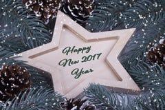 Bożenarodzeniowego nowego roku Wakacyjny kartka z pozdrowieniami z drewnianymi pięć wskazującymi gwiazdowymi jodeł gałąź rożkami  Zdjęcie Royalty Free