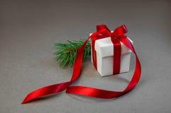 Bożenarodzeniowego prezenta Białego pudełka gałąź Czerwonego Tasiemkowego Jedlinowego zmroku Popielaty tło Nowego roku wakacje sk Fotografia Royalty Free