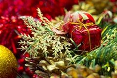 Bożenarodzeniowej teraźniejszości ornament na czerwonym świecidełku i zieleni szpilce opuszcza Zdjęcie Stock
