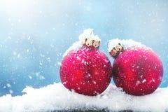 Bożenarodzeniowi baubles lub dekoracje na śniegu na zimy jaskrawych półdupkach Obraz Stock