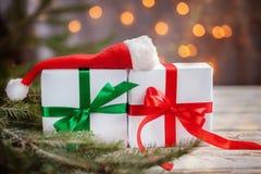 Bożenarodzeniowi biali pudełka lub presentes z Santa kapeluszem na białym drewnianym stole zdjęcie royalty free