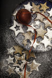 Bożenarodzeniowi ciastka kropiący cukierem na talerzu z czerwonym jabłkiem. Obraz Royalty Free