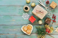Bożenarodzeniowi domowej roboty prezenty, ciastka, boże narodzenie piłki, retro nożyce na zielonym drewnianym nieociosanym tle Od zdjęcia stock