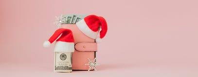 Bożenarodzeniowi koszty Różowa rzemienna kiesa z Santa Claus nakrętką, prezentem, jedlinowym drzewem i dolarami banknotów na różo obrazy royalty free
