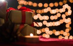 Bożenarodzeniowi prezentów pudełka, świeczka na czerwonym szaliku z bokeh i zaświecają tło Zdjęcie Stock