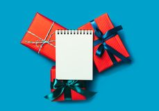 Bożenarodzeniowi prezentów pudełka i pusty notatnik na turkusowym tle obrazy stock